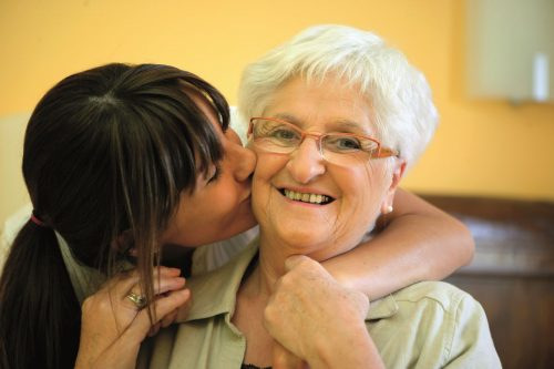 Portrait of a young woman kissing a smiling senior woman on the cheek